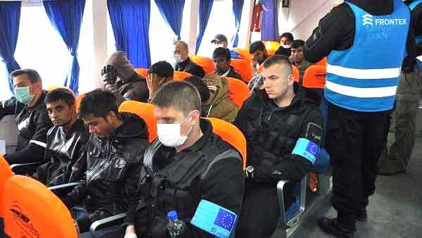 Refugiados e agentes do Frontex no ferry de volta para a Turquia.